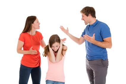 Das Foto zeigt Expartner, eine Frau und ein Mann, im Streit. Die Tochter hält sich die Ohren zu.