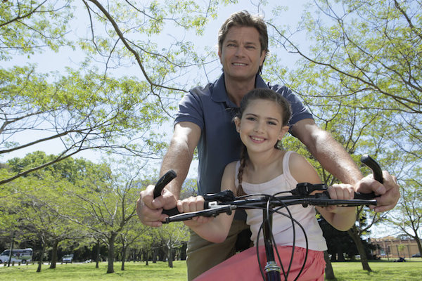 Das Foto zeigt einen Vater, der viel Spaß mit seiner Tochter am Rad hat. Durch gute Erziehung kann eine gute Beziehung zu den Kindern möglich werden.