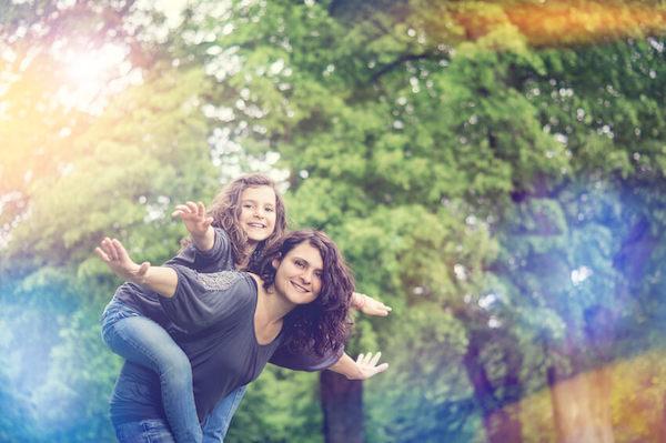 Das Foto zeigt eine Mutter mit einem Kind auf ihrem Rücken, beide glücklich miteinander, da Familie und Beruf in Balance sind.