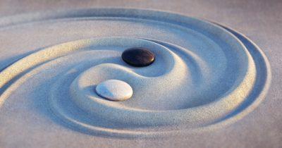 Das Foto zeigt ein mit Sand und zwei Steinen dargestelltes Yin und Yang Symbol. Die Steine sind weiß und schwarz. Dieses Symbol steht für die systemischen Werte in der Beratung.