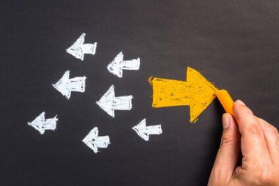 Das Bild zeigt kleine Pfeile in eine Richtung und einen großen Pfeil in die andere Richtung. Es symbolisiert, dass eine neuer Job oder neue berufliche Ziele Burnout vermeiden können.