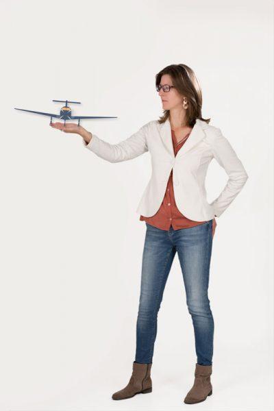 Das Foto zeigt Daniela Elsinger mit einem Flugzeug als Symbol für losstarten