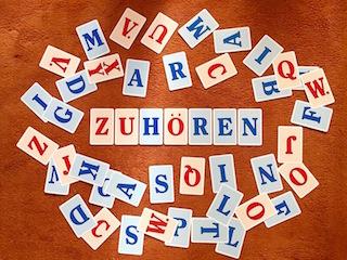 """Das Foto zeigt Buchstaben und das Wort """"zuhören"""" als Symbol für gelungene gewaltlose Kommunikation."""