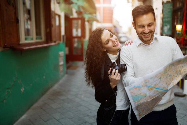 Das Foto zeigt ein glückliches Paar auf Reisen mit einer Landkarte und einem Fotoapparat. Paarberatung kann eine glückliche Beziehung zum Partner möglich machen.