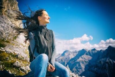 Das Foto zeigt eine Frau am Berg, sie wirkt glücklich und zufrieden mit sich und der Welt. Psychologische Beratung unterstützt einen besseren Umgang mit Stress.